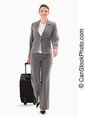 Businesswoman walking forward with a suitcase - A...