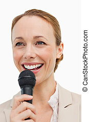 Enthusiastic woman in a suit speaking with a microphone...