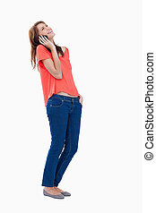 Relaxed teenage girl tilting her head while makng a call -...