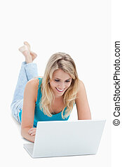 A smiling woman with a laptop is lying on the ground with her legs up against a white background