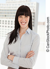 A smiling business woman with her arms folded - A woman...