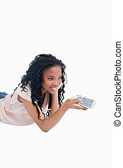 A smiling young girl is lying on the floor holding a television remote control