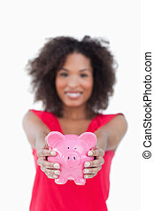 Pink piggy bank being held by a brunette woman