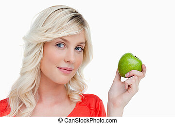 Beautiful woman holding a delicious green apple while looking at the camera