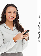 Portrait of a brunette smiling while using her mobile