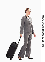 Smiling businesswoman with suitcase walking - A smiling...