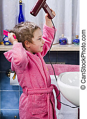 Girl dries her hair with hair dryer