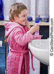 Little girl who puts the cream on your face in the bathroom