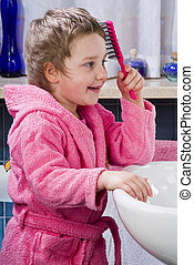 Little girl combing her hair with a brush in the bathroom