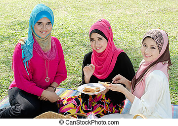 Beautiful Muslim girlfriends on picnic at sunny day