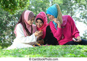 young muslim woman in head scarf meet friends and using...
