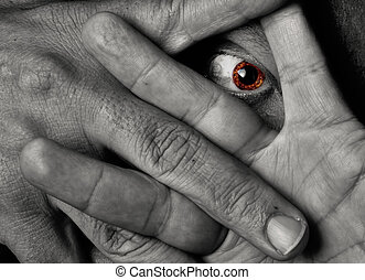 Yellow eye staring throug fingers - Spooky yellow eye of a...