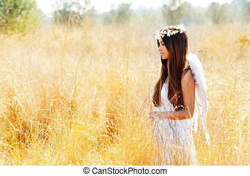 Angel girl in golden field with feather white wings - Angel...