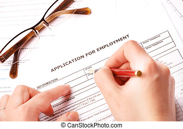 Completing an employment application.Glasses in the...