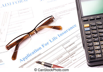 Life insurance application form with fountain pen, glasses...
