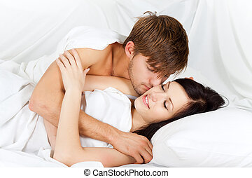 young couple - young lovely couple lying in a bed, happy...