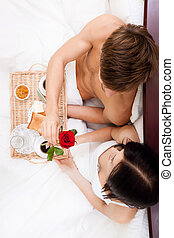 young couple - beautiful young happy couple lying in bed