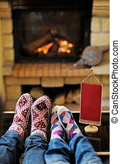 happy Young romantic couple sitting on sofa in front of fireplace at winter season in home