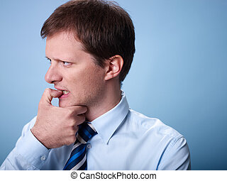 nervous business man biting finger nails - stressed mid...