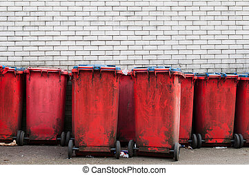 Garbage bins - many red dirty garbage bins against a gray...