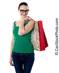 Smiling young female carrying shopping bags on her shoulders