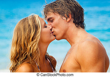 Young Couple Kissing on Tropical Beach - Attractive Young...