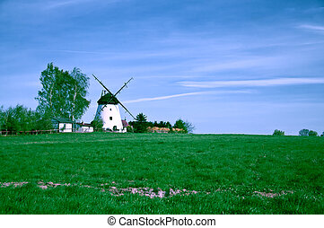 white windmill on the green farm field