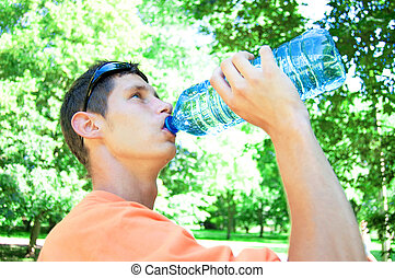 Thirst. - Young man drinking water in heat.