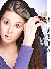 hair care - young woman use hair straightener iron, studio...