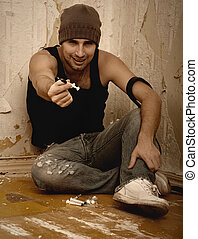 bad man - drug dealer with syringes and with drugs sitting...