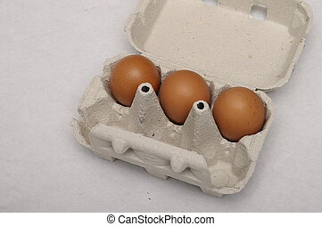 Cardboard egg carton and three eggs