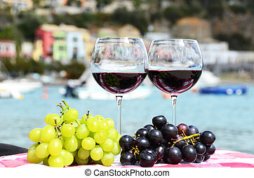 Pair of wineglasses and grapes against the harbour of Portvenere, Italy