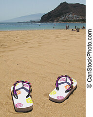 Flip-flops on the sand of Teresitas beach Tenerife island,...