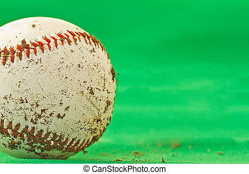 Baseball - A dirty baseball over a green background