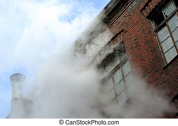 The old brick building was destroyed, smoke and steam from...