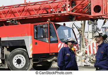 mobile cranes and workers - building workers with giant...