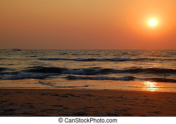 Sunset in Goa in India - Empty beach, boat in the sea, waves...