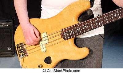 Close-up of female hand, playing the bass guitar