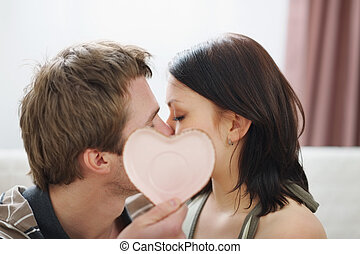Kissing couple hiding behind Valentines heart