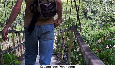 Walking the Old Suspension Bridge - Man walks across an old,...