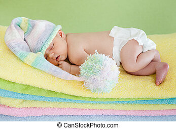 newborn baby girl weared cap sleeping on colourful towels -...