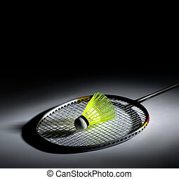 Shuttlecock and badminton on dark background