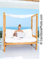 Woman on canopied seat with laptop