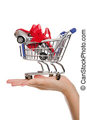 Cars and gift ribbon in shopping trolley on palm - Cars in...
