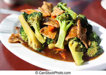 Plate of broccoli with vegan seitan as a meat substitute.