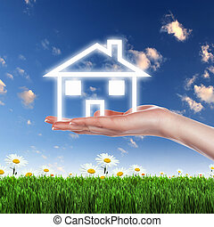 House and human hand against blue sky