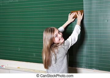 Smiling girl cleaning school blackboard