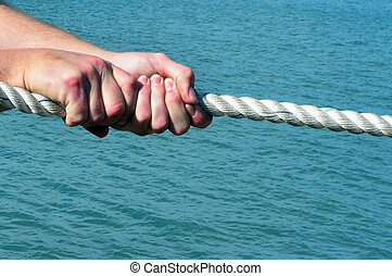 Sport - Rope Pulling - Close up of hands pulling a rope.