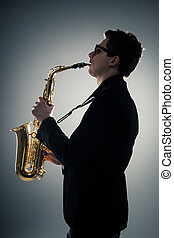Saxophone - Young man playing sax in the dark