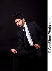 young successful business man with a suit isolated on black background